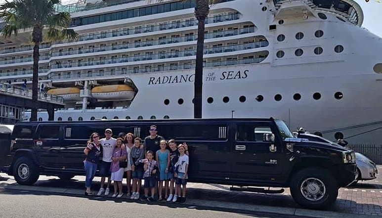 Family posing with the Hummer Limo with a Cruise in the background